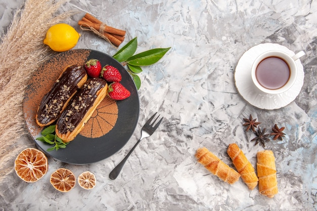Draufsicht leckere schoko-eclairs mit tasse tee auf weißem keks-dessert-keks