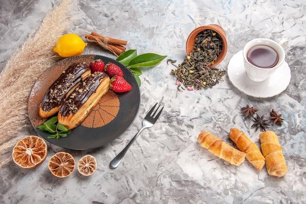 Draufsicht leckere schoko-eclairs mit tasse tee auf weißem kekskuchen dessertkeks