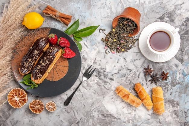 Draufsicht leckere schoko-eclairs mit tee auf weißem kekskuchen-dessert-keks