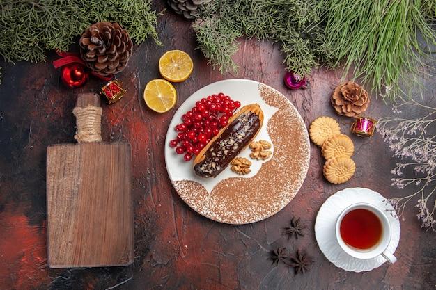 Draufsicht leckere schoko-eclairs mit tee und beeren auf dem dunklen tisch süßer kuchen-kuchen-nachtisch