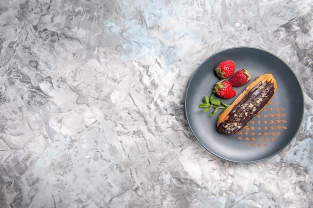Draufsicht leckere schokoladen-eclairs mit erdbeeren auf hellem dessertkuchen-fruchtkuchen
