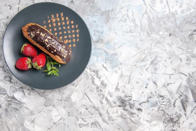 Draufsicht leckere schokoladen-eclairs mit erdbeeren auf hellem schreibtisch dessertkuchen obst