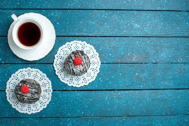 Draufsicht leckere schokoladenbällchen mit tasse tee auf blauem rustikalem schreibtischteekuchen-kekskeks süß