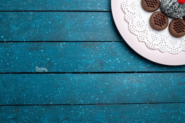 Draufsicht leckere schokoladenkekse mit schokoladenkuchen auf blauen rustikalen schreibtischkuchen kakaotee süße kekskekse