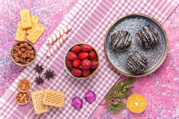 Draufsicht leckere schokoladenkuchen mit erdbeeren auf rosa