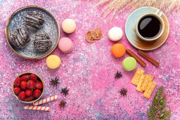 Draufsicht leckere schokoladenkuchen mit französischen macarons auf dem rosa
