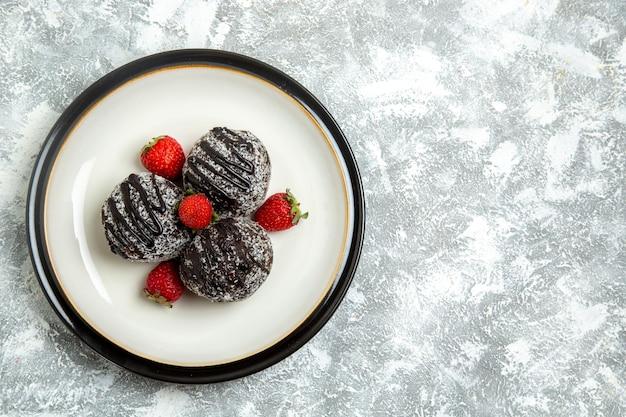 Draufsicht leckere schokoladenkuchen mit frischen roten erdbeeren auf weißer oberfläche