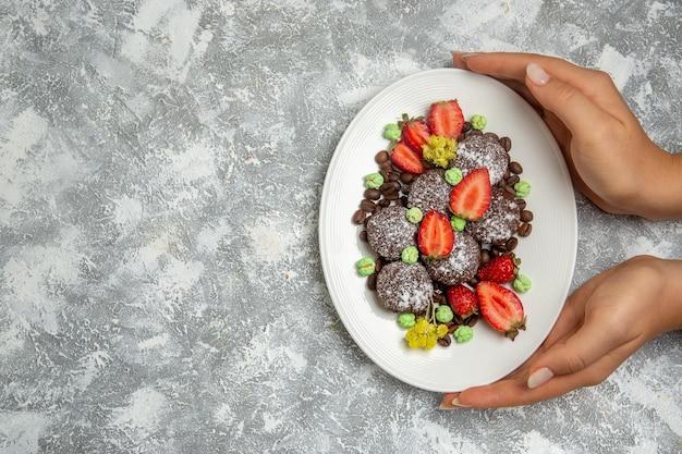 Draufsicht leckere schokoladenkuchen mit frischen roten erdbeeren und schokoladenstückchen auf weißer oberfläche
