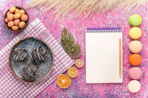 Draufsicht leckere schokoladenkuchen mit macarons auf dem rosa