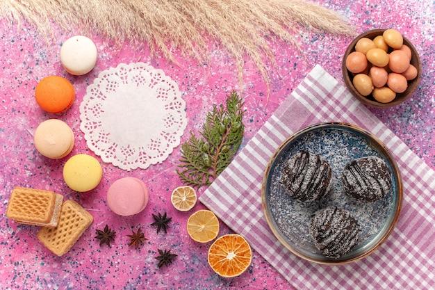 Draufsicht leckere schokoladenkuchen mit macarons und waffeln auf rosa