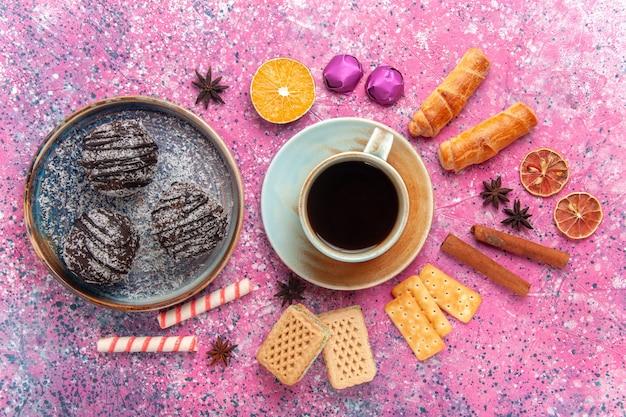 Draufsicht leckere schokoladenkuchen mit süßigkeiten und tasse tee auf rosa