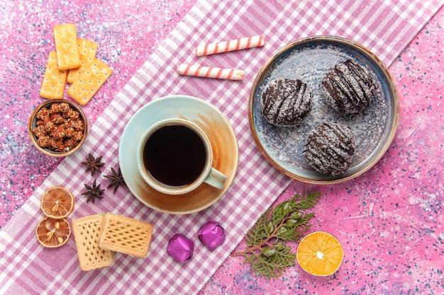 Draufsicht leckere schokoladenkuchen mit tasse tee auf dem rosa