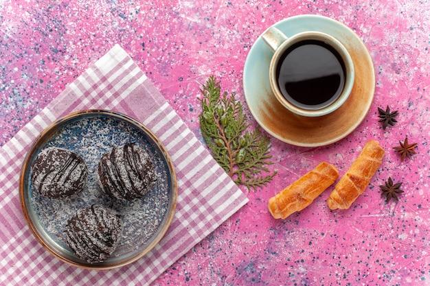 Draufsicht leckere schokoladenkuchen mit tasse tee und bagels auf rosa