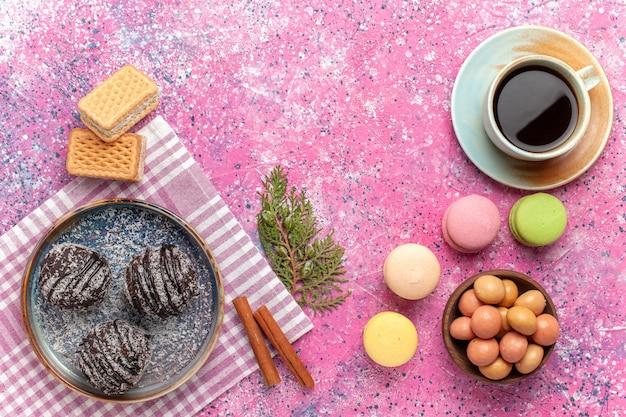 Draufsicht leckere schokoladenkuchen mit tasse tee und macarons auf rosa