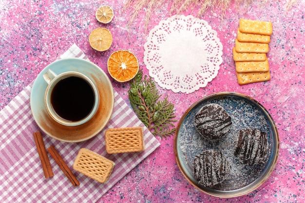 Draufsicht leckere schokoladenkuchen mit tasse tee und waffeln auf hellrosa