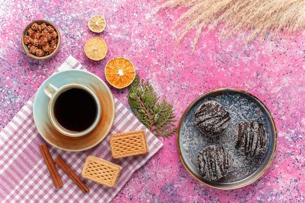 Draufsicht leckere schokoladenkuchen mit tasse tee waffeln auf rosa
