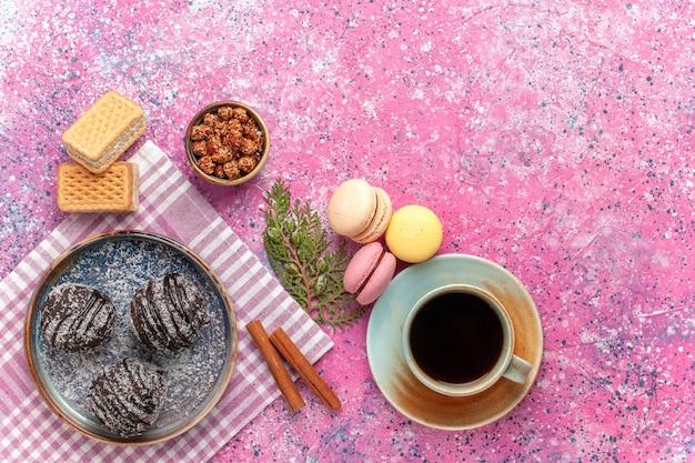 Draufsicht leckere schokoladenkuchen mit tee und macarons auf rosa