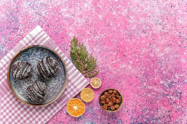 Draufsicht leckere schokoladenkuchen mit zitronenscheiben auf rosa