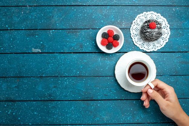 Draufsicht leckere schokoladenkugel mit tasse tee auf blau rustikalem schreibtisch tee kuchen keks keks süß