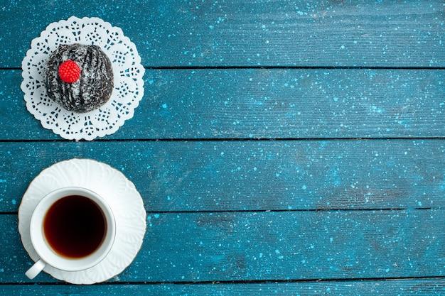 Draufsicht leckere schokoladenkugel mit tasse tee auf blauem rustikalem schreibtischtee süßer kuchenplätzchenkeks