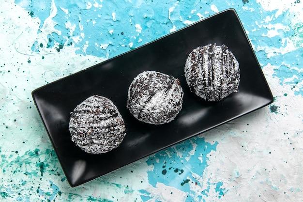 Draufsicht leckere schokoladenkugeln schokoladenkuchen mit zuckerguss auf blauem schreibtisch