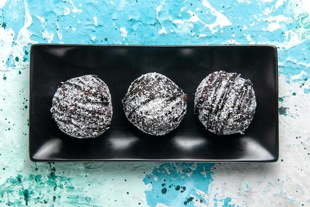 Draufsicht leckere schokoladenkugeln schokoladenkuchen mit zuckerguss auf der blauen oberfläche