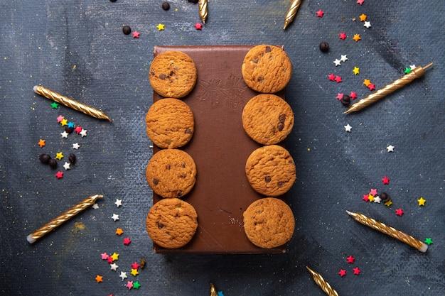 Draufsicht leckere schokoladenplätzchen auf dem braunen fall mit kerzen auf dem dunkelgrauen schreibtischkekskeks süßer tee