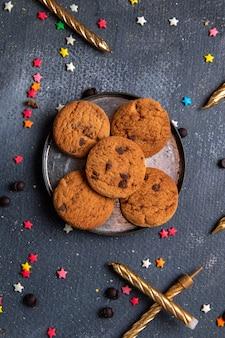 Draufsicht leckere schokoladenplätzchen innerhalb platte mit bunten kleinen sternzeichen und kerzen auf dem dunklen hintergrundplätzchenkekszuckersüßtee