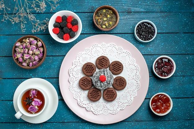 Draufsicht leckere schokoladenplätzchen mit marmelade und tasse tee auf blauem rustikalem schreibtischkuchen kakaotee süßer keksplätzchen