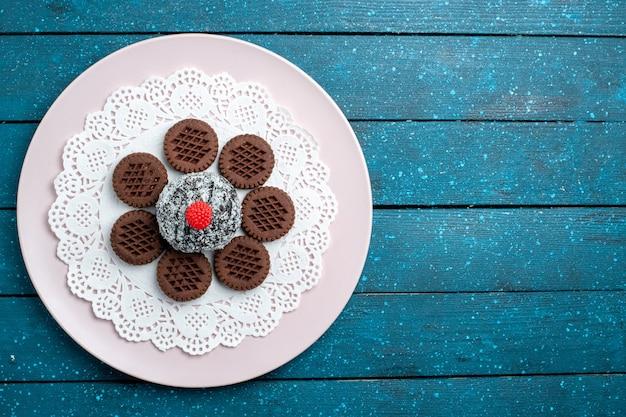 Draufsicht leckere schokoladenplätzchen mit schokoladenkuchen auf dem blauen rustikalen schreibtischkuchen-kakaotee süßer keksplätzchen