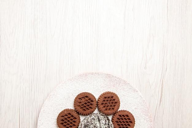 Draufsicht leckere schokoladenplätzchen mit wenig kakaokuchen auf weiß