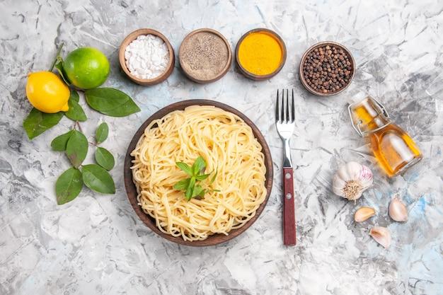 Draufsicht leckere spaghetti mit gewürzen auf einem weißen schreibtischteiggericht nudelgericht