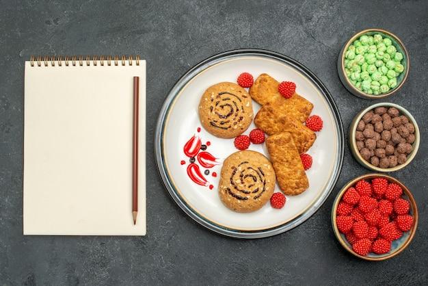 Draufsicht leckere süße kekse mit anderen süßen süßigkeiten auf grauem hintergrundkeks süßer zuckerkuchenplätzchentee