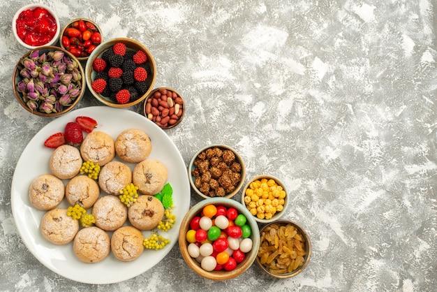 Draufsicht leckere süße kekse mit bonbons und nüssen auf weißem hintergrund süßigkeitenplätzchenkeks süßer teezucker