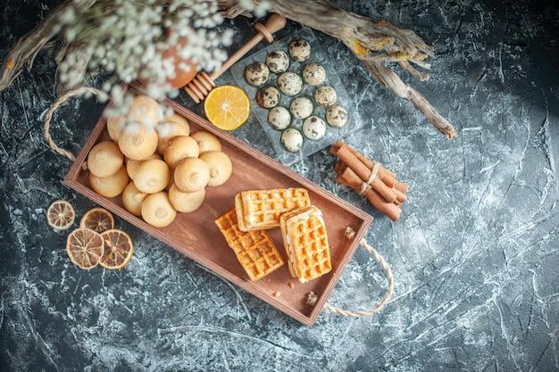 Draufsicht leckere süße kekse mit kleinen kuchen auf hellgrauer hintergrundfarbe süßer kuchenzuckerplätzchen-nusskuchen