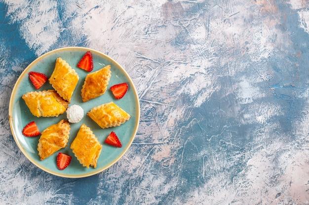Draufsicht leckere süße kuchen mit erdbeeren auf blauem boden