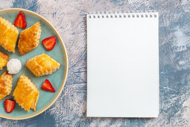 Draufsicht leckere süße kuchen mit erdbeeren auf blauem hintergrund Kostenlose Fotos