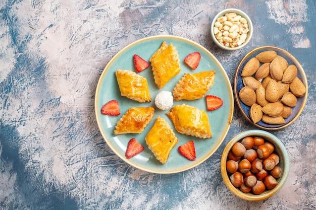 Draufsicht leckere süße kuchen mit nüssen auf blauem hintergrund