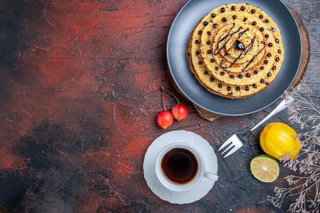 Draufsicht leckere süße pfannkuchen mit schokoladenglasur auf dunklem schreibtisch