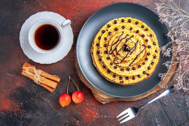 Draufsicht leckere süße pfannkuchen mit tasse tee auf dunkler oberfläche