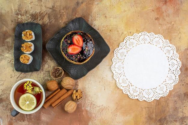 Draufsicht leckere süße pfannkuchen mit tasse tee auf holzschreibtisch