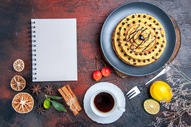 Draufsicht leckere süße pfannkuchen mit tee auf der dunklen oberfläche