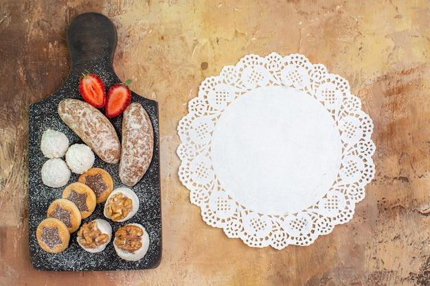 Draufsicht leckere süßigkeiten mit keksen auf holzschreibtisch