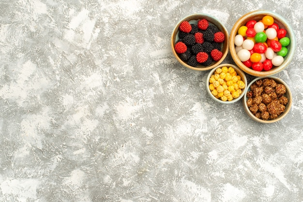 Draufsicht leckere süßwaren mit nüssen und süßigkeiten auf hellem hintergrundzuckertee süßer kuchenplätzchen