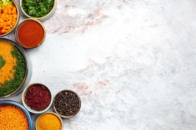 Draufsicht leckere suppe mit gemüse und verschiedenen gewürzen auf einem weißen hintergrundmahlzeit-nahrungsmittelsuppengemüse