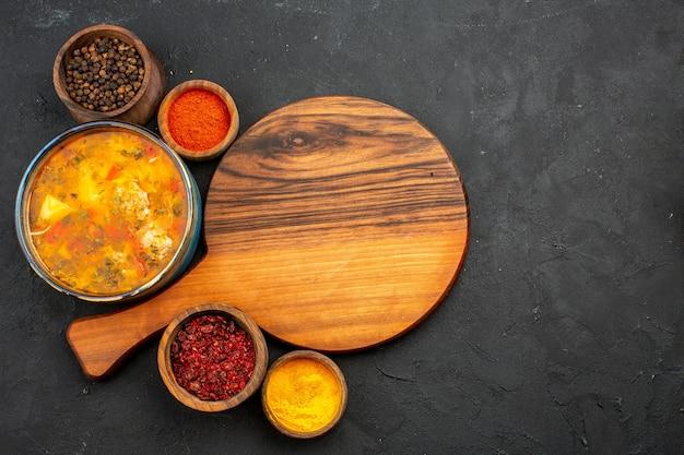Draufsicht leckere suppe mit verschiedenen gewürzen auf dem grauen hintergrund suppenmahlzeit lebensmittel fleischgewürz würzig
