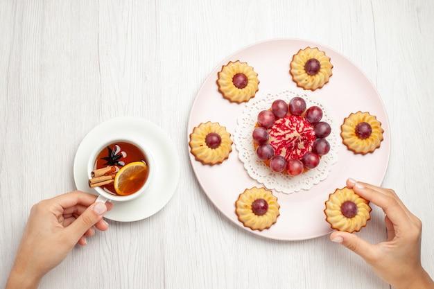 Draufsicht leckere traubenplätzchen mit tasse tee auf weißem tisch, süßer nachtischkekstorte