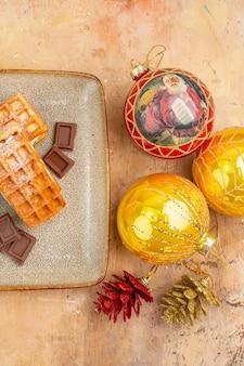 Draufsicht leckere waffelkuchen mit schokolade und neujahrsbaumspielzeug auf dem hellen hintergrund