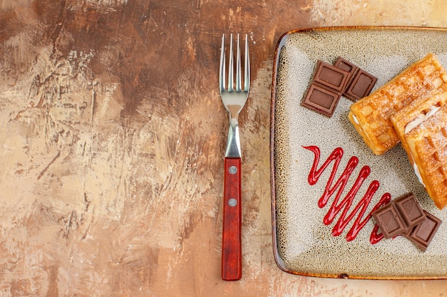 Draufsicht leckere waffelkuchen mit schokoriegeln auf braunem hintergrund