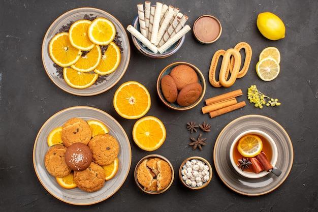 Draufsicht leckere zuckerkekse mit tasse tee und geschnittenen frischen orangen auf dunklem hintergrund zuckertee-fruchtkeksplätzchen süß